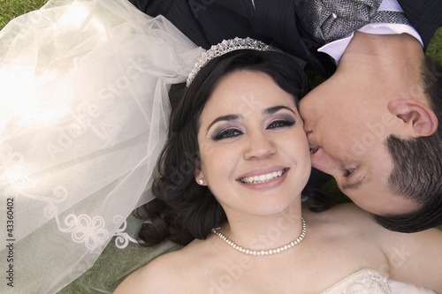 Hispanic bride and groom laying on ground