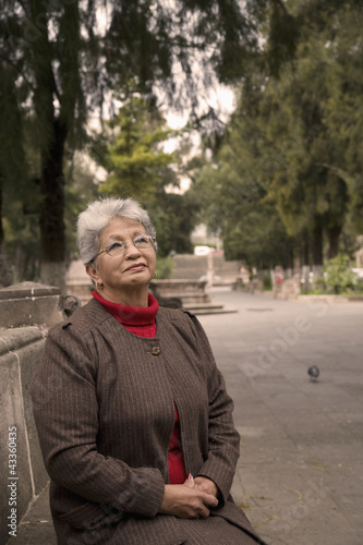 Senior Hispanic woman sitting in park