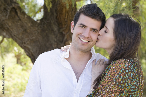Hispanic woman kissing boyfriend outdoors