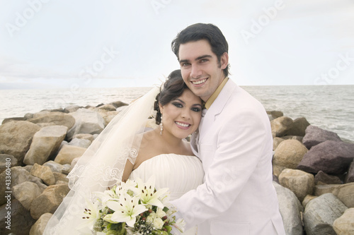 Hispanic bride and groom hugging