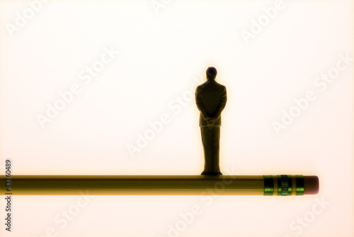 Figure of businessman balanced on pencil