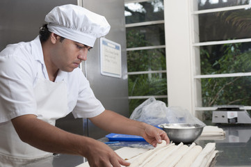 Hispanic baker working in commercial kitchen