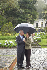 Hispanic couple standing together under umbrella