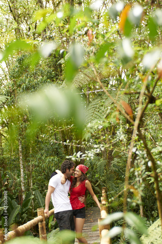 Hispanic couple hugging in forest on wooden walkway