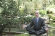 Hispanic businessman practicing yoga in park