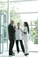 Hispanic business people talking to doctor in lobby