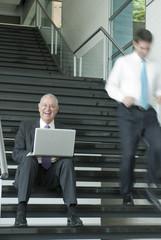 Hispanic businessman using laptop on staircase