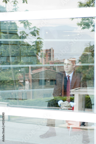 Hispanic businessman looking out window