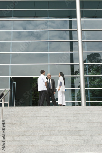 Hispanic business people talking to doctor on steps