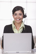 Hispanic businesswoman in headset working at desk in office