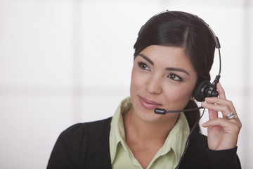 Hispanic businesswoman talking on headset