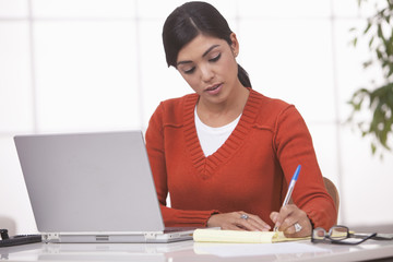 Hispanic businesswoman writing on notepad