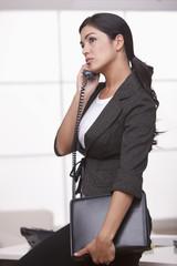 Hispanic businesswoman talking on telephone