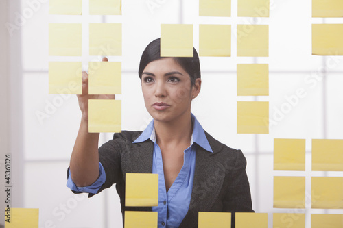 Hispanic businesswoman looking at sticky notes