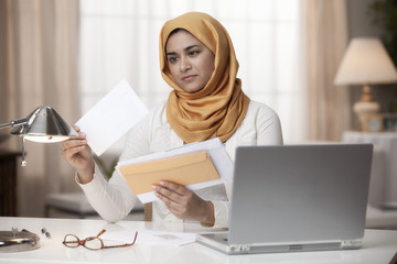 Mixed race woman in hijab looking at mail