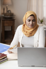 Mixed race woman in hijab studying on laptop