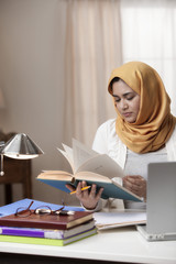 Mixed race woman in hijab reading book