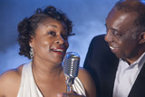 African American couple singing together into microphone