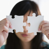 Korean woman holding two puzzle pieces