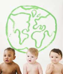 Babies sitting together with drawing of globe on wall