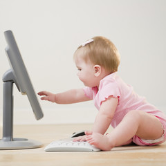 Caucasian baby playing with computer