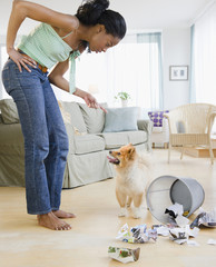 Mixed race woman scolding Pomeranian dog next to garbage