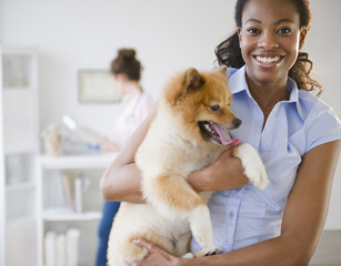 Mixed race woman holding Pomeranian dog