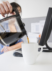 Korean woman pouring coffee at desk