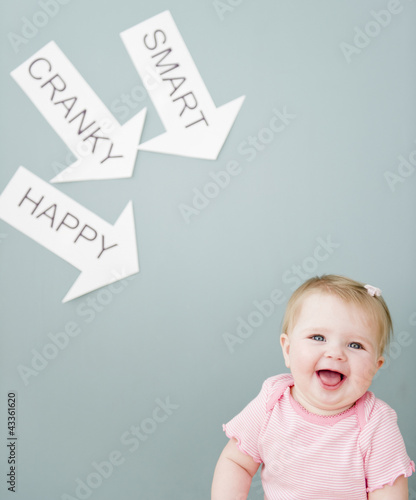 Caucasian baby near arrows reading cranky, smart and happy
