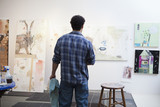 Mixed race artist looking at paintings in studio