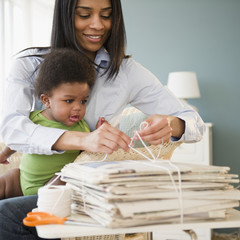 African American mother holding baby on lap and tying newspapers
