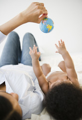 African American mother showing globe to baby boy