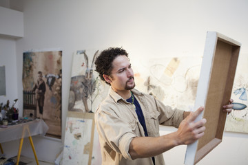 Mixed race artist holding painting in studio