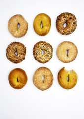 Various bagels, one with bite missing
