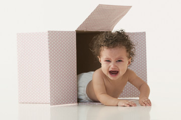 Crying mixed race baby girl laying in box