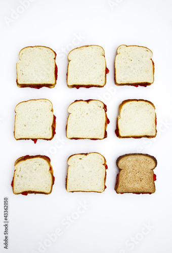 Peanut butter and jelly sandwiches, one on whole wheat bread