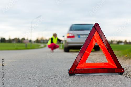 Junge Frau mit Warndreieck auf Straße