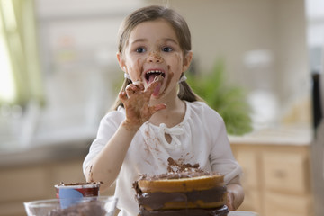 Mixed race girl frosting cake and licking fingers
