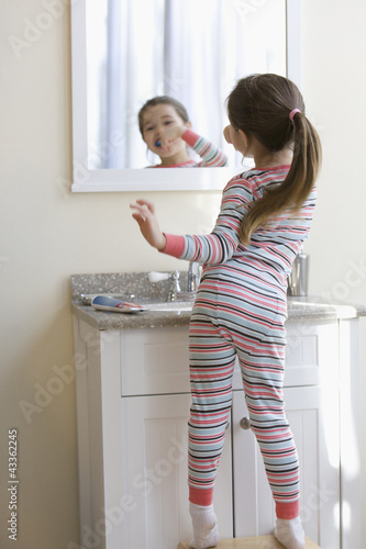 Mixed race girl brushing teeth