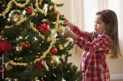 Mixed race girl decorating Christmas tree