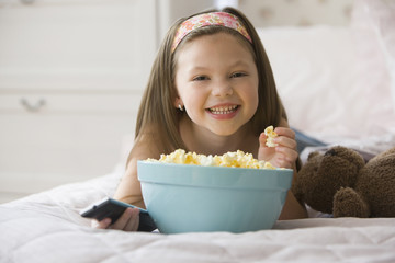 Caucasian girl on bed eating popcorn and watching television