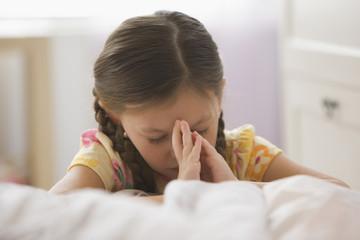 Caucasian girl kneeling by bed praying