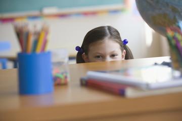 Caucasian girl behind desk in classroom