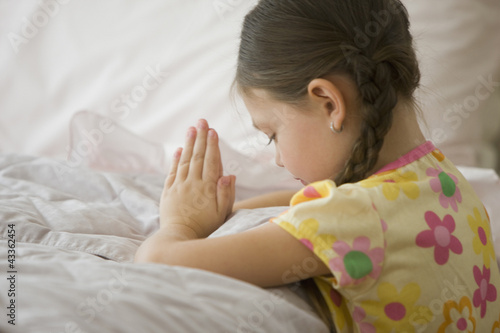 Caucasian girl kneeling by bed praying