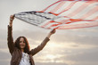 Caucasian woman holding flapping American flag