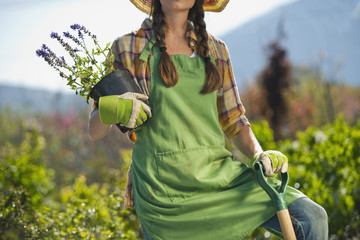 Caucasian woman standing with shovel and flowers in plant nursery