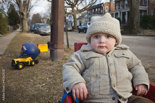Boy in coat and cap sitting in yard