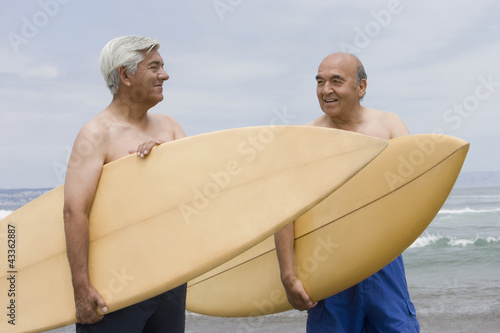 Senior Hispanic men holding surfboards on beach