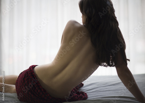 Topless Caucasian woman sitting on bed