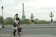Caucasian couple walking across bridge with Eiffel Tower in background